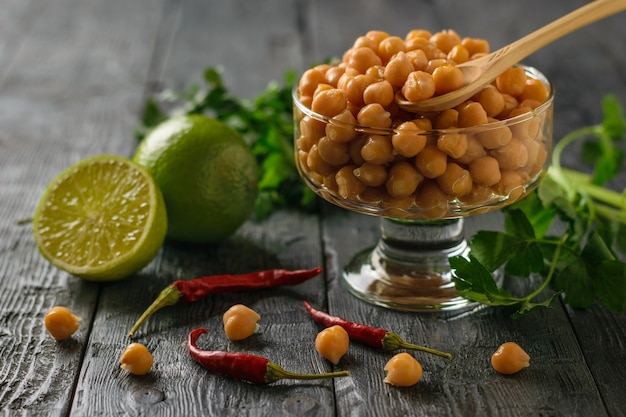 Boiled chickpeas in a glass bowl, pepper, herbs and lime on a wooden table. Premium Photo