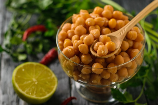 Boiled chickpeas in a glass bowl, pepper and lime on a table. vegetarian cuisine from legumes. Premium Photo