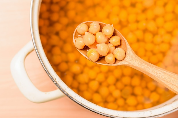 Boiled chickpeas in a wooden spoon and in a pot on a yellow table. vegetarian cuisine from legumes. the view from the top. Premium Photo