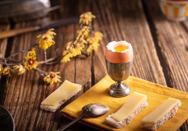 나무 테이블에 빵과 치즈와 은색 껍데기에 삶은 계란 프리미엄 사진