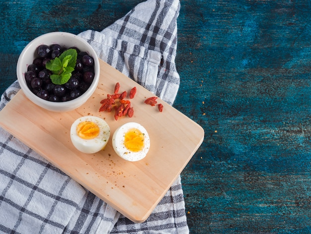 Boiled egg with berries on wooden board Free Photo