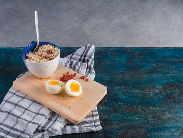 Boiled egg with oatmeal on wooden board Free Photo