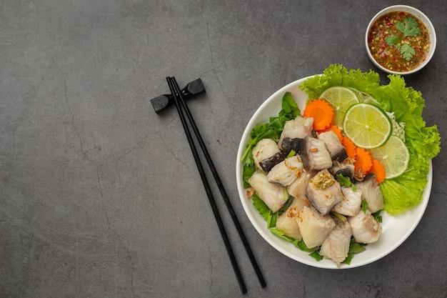 魚の煮物にスパイシーなディップソースと野菜を添えて 無料写真
