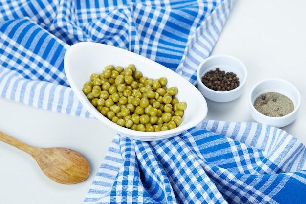 Зеленый горошек отварной в белой миске со специями, ложкой и скатертью. Бесплатные Фотографии