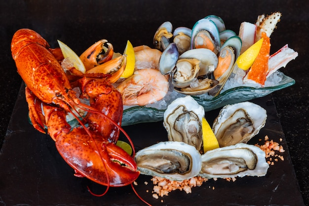 Boiled lobster, fresh oysters, shrimps, mussels and clams served in black stone plate. Premium Photo