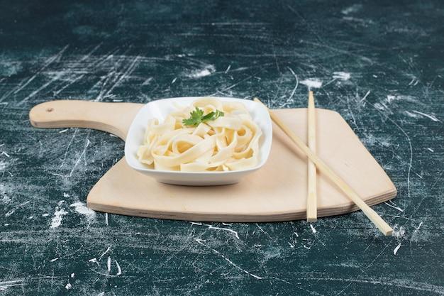 젓가락으로 흰 그릇에 삶은 Tagliatelle 파스타. 무료 사진