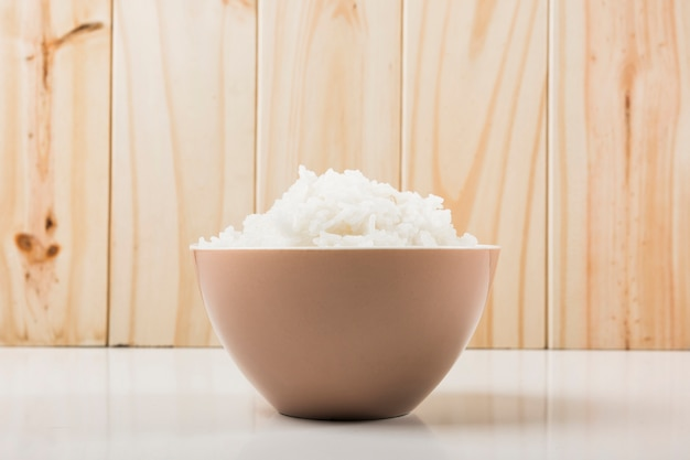 Boiled white rice in the bowl on white table against wooden background Free Photo