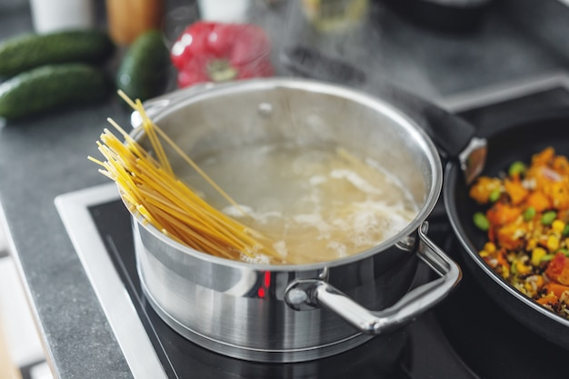 Boiling pot with cooking spaghetti pasta in the kitchen. closeup Free Photo