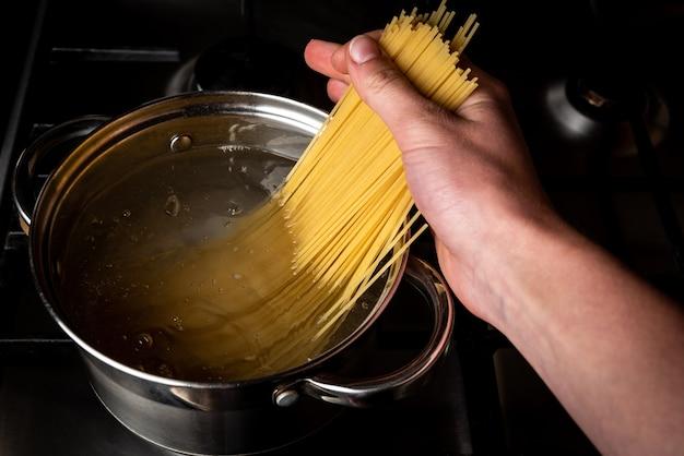 Варка спагетти в кастрюле на плите на кухне. Premium Фотографии