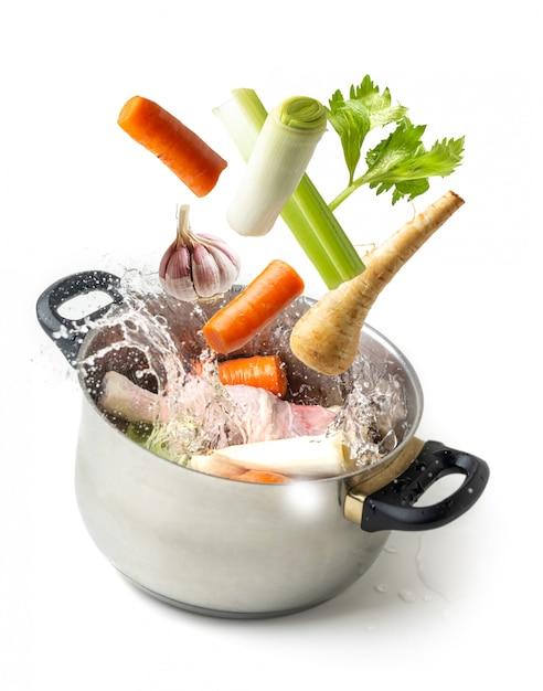 分離された白の鍋に向かって飛んで野菜を沸騰 Premium写真