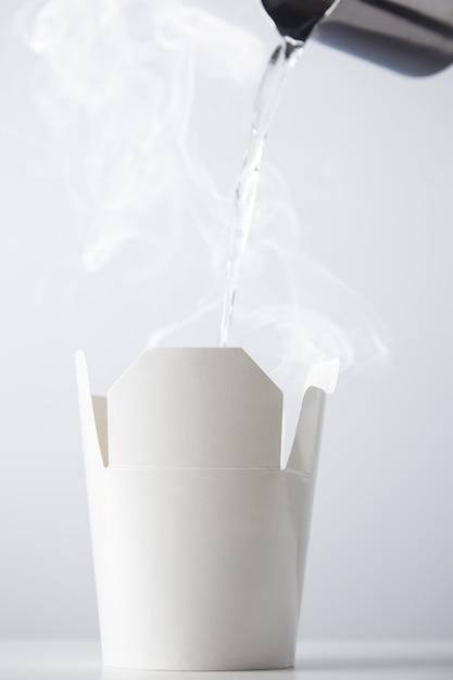 스테인레스 스틸 주전자에서 흰색 골판지라면 상자 용기에 끓는 물을 부어 화이트 절연 무료 사진