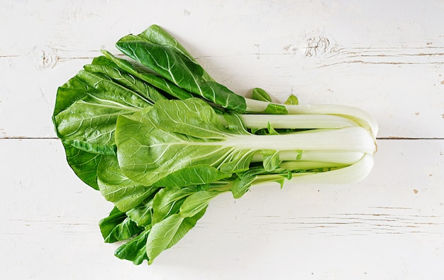 Bok choy or chinese-cabbage on white wooden table. pak choi. top view Premium Photo