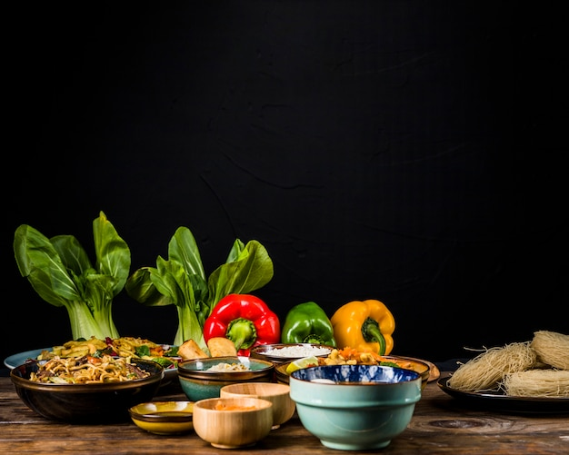 Bokchoy; bell peppers and thai traditional food on table against black background Free Photo