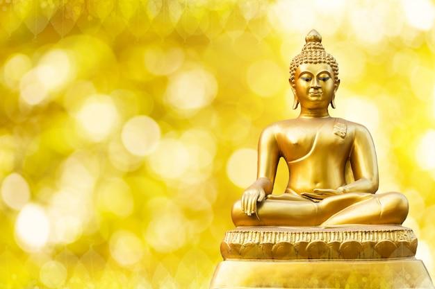 Красивый золотой статуи будды на золотом желтом bokeh. Premium Фотографии