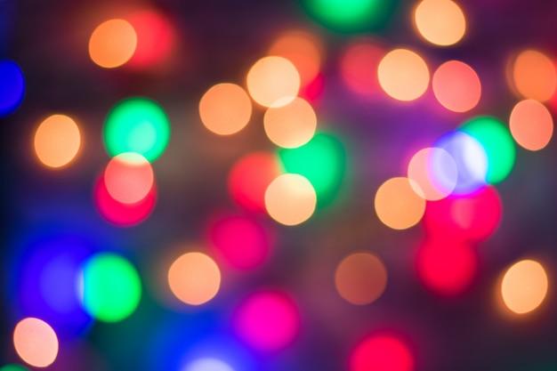 Абстрактное пестротканое bokeh на черной предпосылке. расфокусированным абстрактные огни новогодний фон. Premium Фотографии