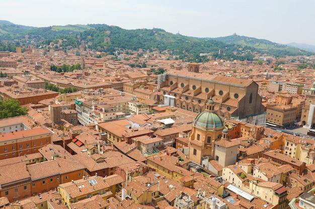 イタリア、ボローニャのマッジョーレ広場にあるサンペトロニオ教会のある古い中世の町の中心部のボローニャの街並み Premium写真