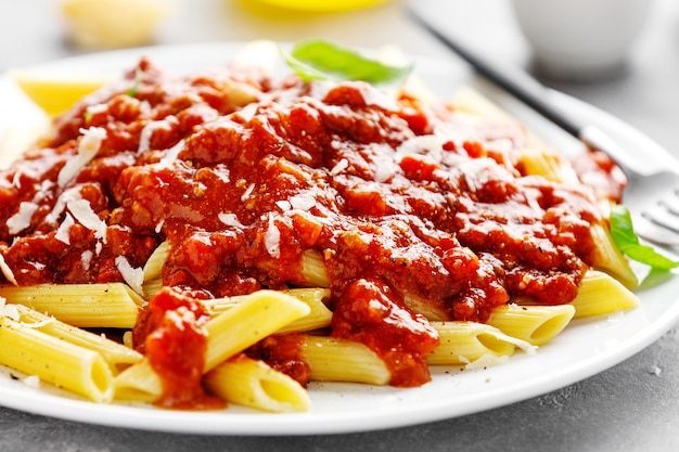 Bolognese penne pasta served on plate Free Photo