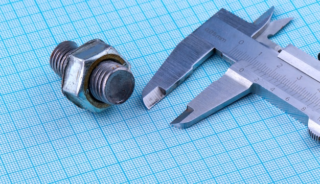 Bolt with nut and caliper on engineering paper. Premium Photo