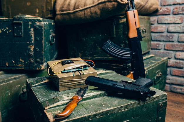 Bomb, knife, gun and rifle on box of ammunition Premium Photo