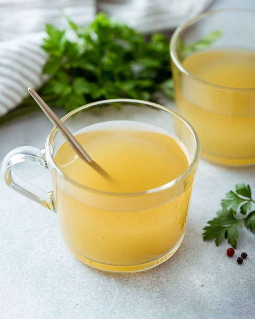 Bone broth in a glass cup on a light background, selective focus Premium Photo