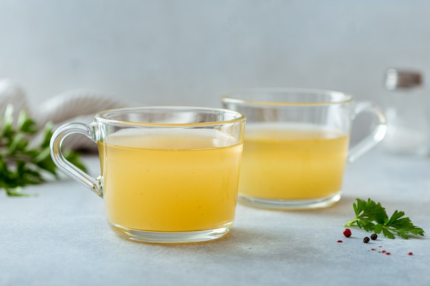 Bone broth in a glass cup on a light table, selective focus Premium Photo