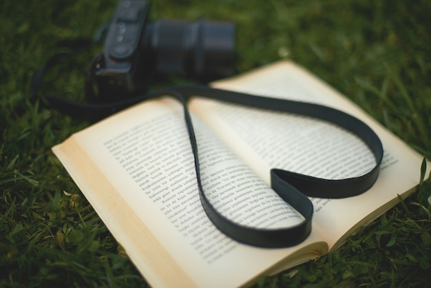 A book and a camera in the park, heart shape Free Photo