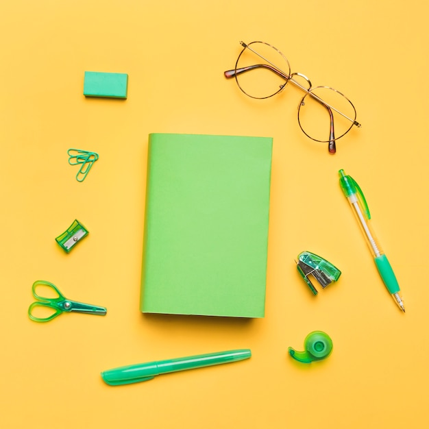 Book in colored cover surrounded by green school supplies Free Photo