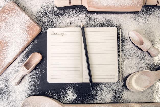 黒の上の道具と小麦粉の周りのレシピの本。上面図。 copyspace。手碑文のレシピ。 Premium写真