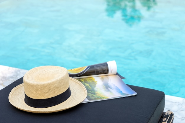 Book and hat on the sun bed near the swimming pool, Premium Photo