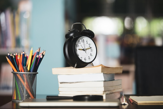 Book, laptop, pencil, clock on wooden table in library, education learning concept Free Photo