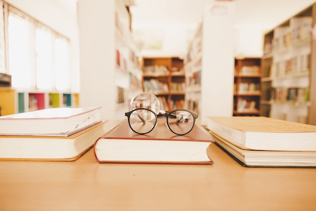 Book in library with old open textbook, stack piles of literature text archive on reading desk Free Photo