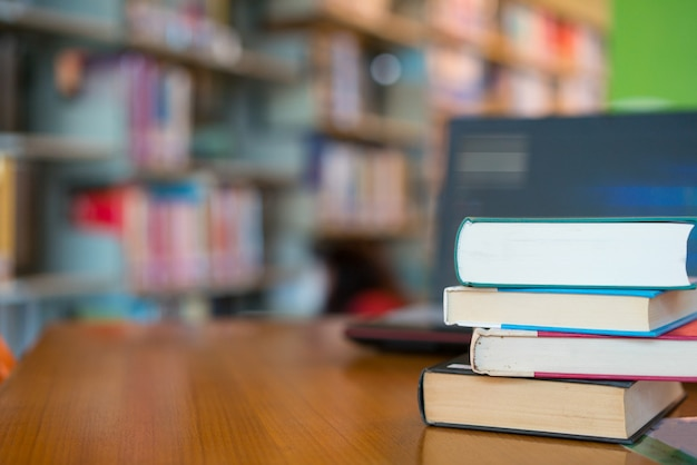 Book in library with old open textbook, stack piles of literature text archive on reading desk Premium Photo