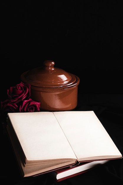 Book mock-up with roses and brown pot Free Photo