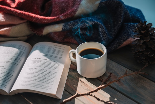 Book near cup and woolen plaid on table Free Photo