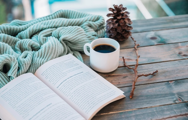 Book near cup and woolen textile on table Free Photo