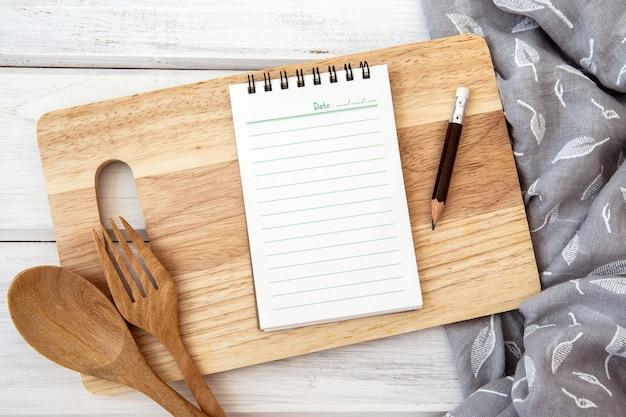 まな板と白いテーブルの上のテーブルクロスの上のメモ帳紙を予約します。 Premium写真