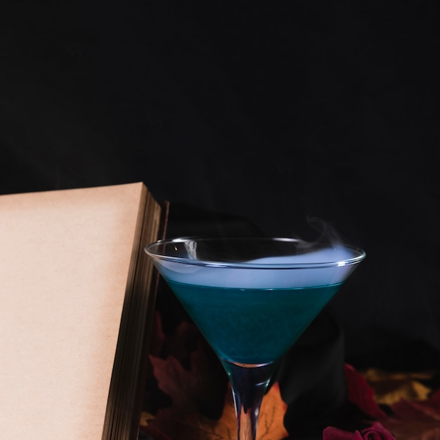 Book with drink on black background Free Photo