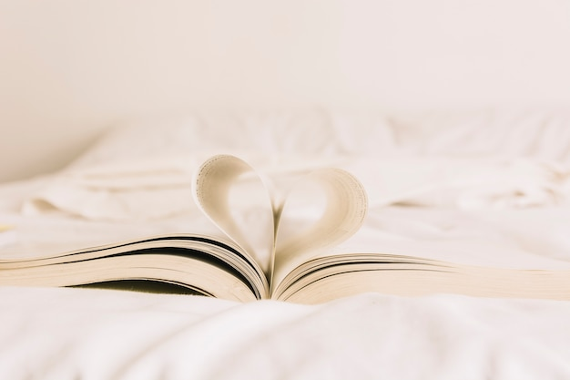 Book with heart lying on bed Free Photo