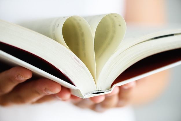 Book with opened pages and shape of heart in girl hands. Premium Photo