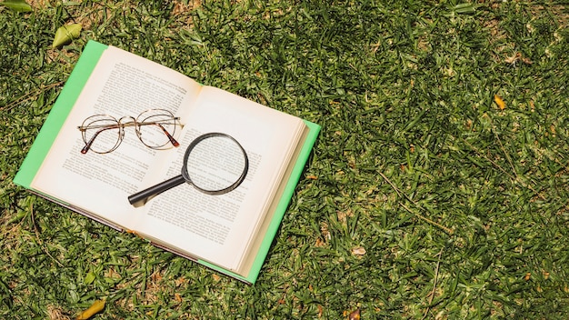 Book with optical implements on green grass Free Photo