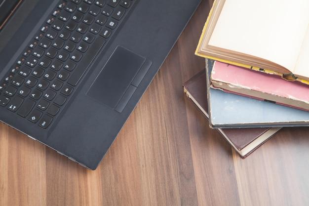 木製のテーブルの本とラップトップインターネット教育ビジネス Premium写真