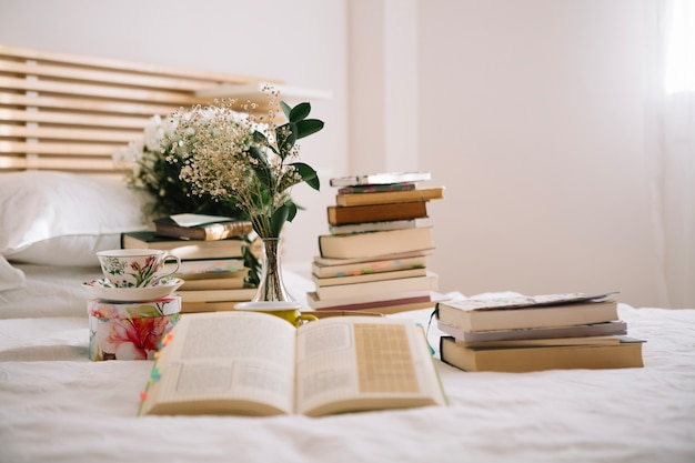 Books and bouquet on bed in morning Free Photo
