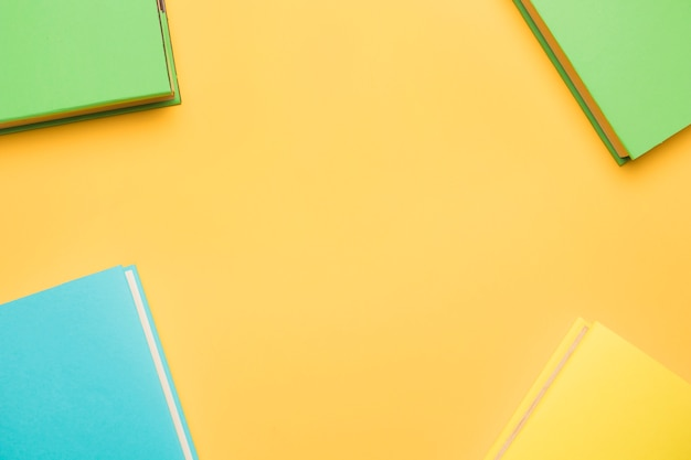 Books in colorful covers on yellow background Free Photo