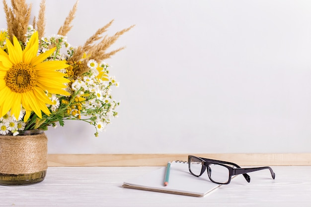 Books, glasses, markers and a bouquet of flowers in a vase on white Premium Photo