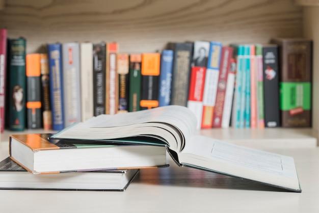 Books lying near bookshelf Free Photo