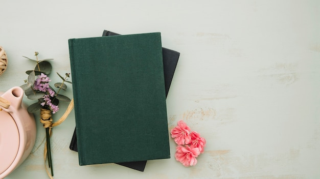 Books near flowers and pot Free Photo