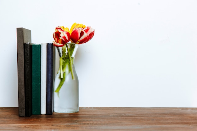 Books near vase with flowers Free Photo