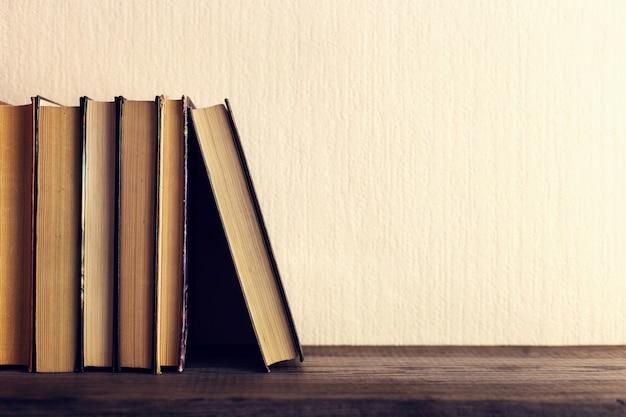Books on the old wooden shelf. Premium Photo