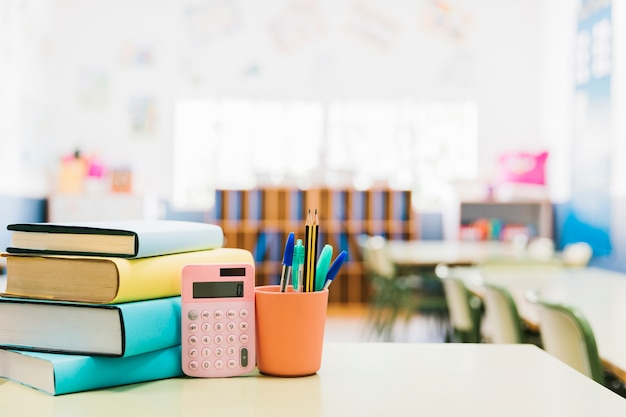 Books and school supplies in cup on table Free Photo