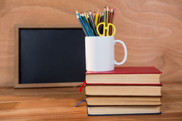Books stack with colored pencil on a mug Photo | Free Download
